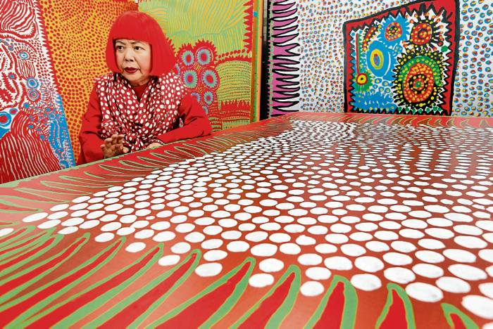 In this photo taken Wednesday, Aug. 1, 2012, Japanese avant-garde artist Yayoi Kusama speaks during an interview at her studio, filled with wall-sized paintings throbbing with her repetitive dots, in Tokyo. Kusama's signature splash of dots has now arrived in the realm of fashion in a new collection from French luxury brand Louis Vuitton - bags, sunglasses, shoes and coats. The latest Kusama collection is showcased at its boutiques around the world, including New York, Paris, Tokyo and Singapore, sometimes with replica dolls of Kusama. (AP Photo/Itsuo Inouye)